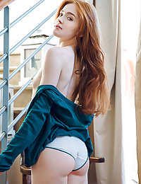 Jia Lissa displays her petite body and pink cock sock on the chair.