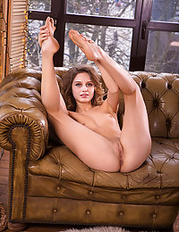 Clarice sensually strips on the couch as she flaunts her small pussy.